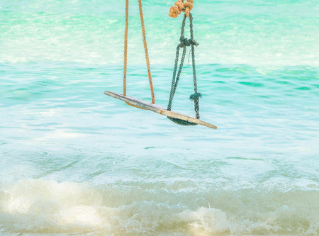 Wooden swing hanging on a branch of tree at the turquoise sea, ThailandExotic tropical paradise swings over crystal blue ocean sea with kayak landscape. Stock fotó