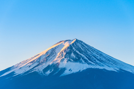 Close-up of Mount Fuji view with Lake Kawaguchi and clear blue sky background in Kawaguchiko, Japan Peak of Fuji mountain cover with snow and shading with golden sunlight in the morning Stock fotó