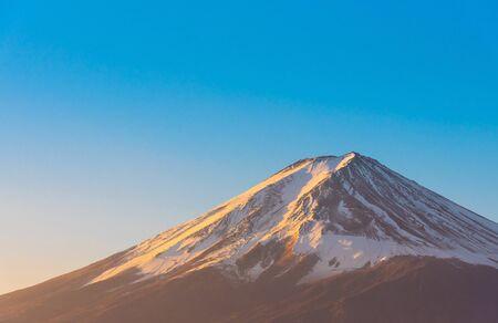 Close-up of Mount Fuji view with Lake Kawaguchi and clear blue sky background in Kawaguchiko, JapanPeak of Fuji mountain cover with snow and shading with golden sunlight in the morning. Stock fotó