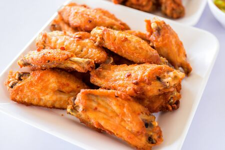 Thai style homemade fried chicken wings on white plate.A plate of fresh, hot, crispy fried chicken.