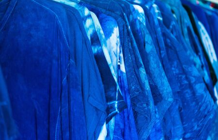 Abstract indigo dyed and contour textured background. Seamless pattern.Shirts on hanger paint abstract batik tie dyed fabric of indigo color, sale at the market, Thailand