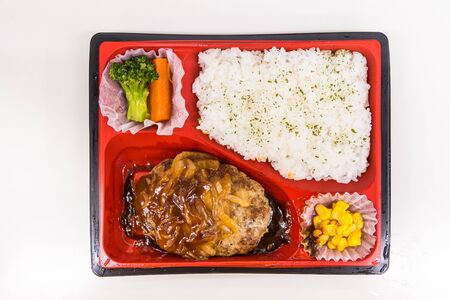 A Japanese Bento Box with rice, vegetables, and teriyaki chicken. Bento boxes are sale in convenience store and train.Japanese food from top view, selected on white background. Stockfoto