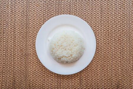 Cooked rice in plate on old wooden table.White jasmine streamed rice in a plate on a wooden table from top-view.Boiled rice