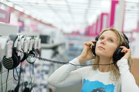 girl listening music with headphones in store