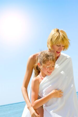 family enjoying beach lifestyle. mother and daughter having fun on the beach photo