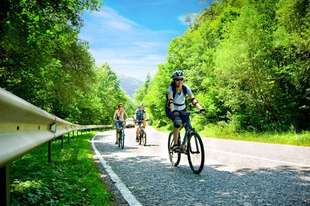three bikers on forest road Stock Photo
