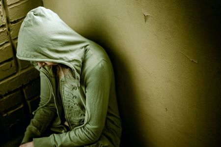 teenage girl siting against wall in a depressed state photo