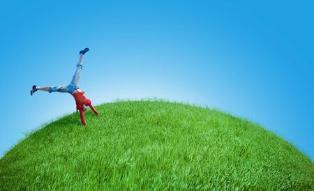 young girl do acrobatic feat on the green hill Stock Photo - 4820193