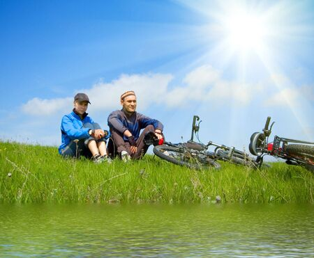 river bank: two cyclists on river bank