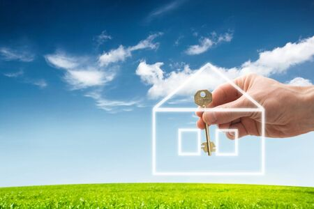 hand holding a house key with a new home photo