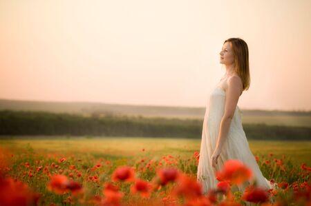 poppy field: vrouw staat in papaverbolkaf veld Stockfoto