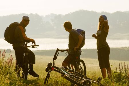 Mixed group of cyclists at sunset photo