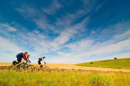 andando en bicicleta: grupo mixto de ciclistas al aire libre Foto de archivo