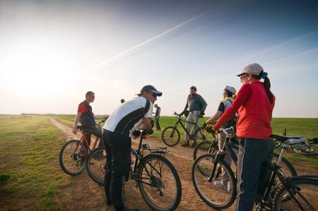 outdoor fitness: Mixed group of cyclists at sunset