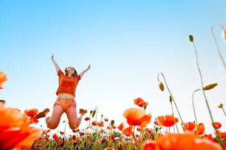 meisje springen in het rood veld klaprozen Stockfoto