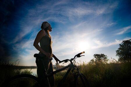 a girl relax biking at sunrise Stock Photo - 5159717