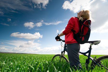 andando en bicicleta: niña con bicicleta en verde campo de verano Foto de archivo