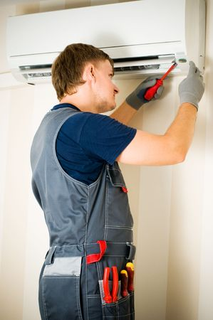 repairmen: a man repair air conditioner