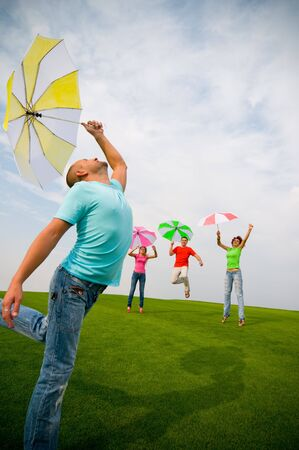young friends jumping with umbrellas photo