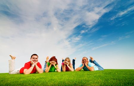 happy teen friends lying on grass Stock Photo - 5553208
