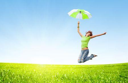 Jeune fille de sauter avec des parapluies