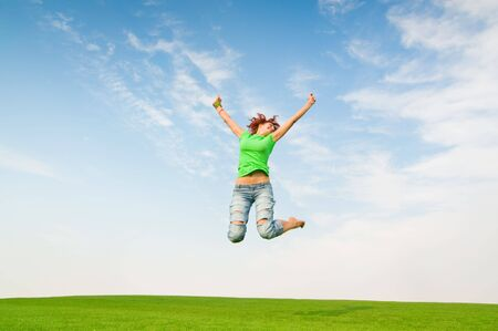 young girl jumping in green field