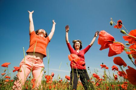 two girls relaxing in poppy field photo