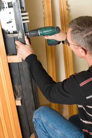 security lock: handyman repairing lock with drill