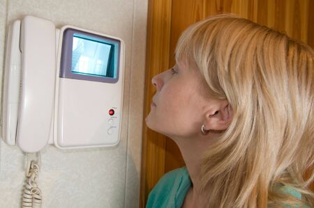 a woman using an intercom Stock Photo