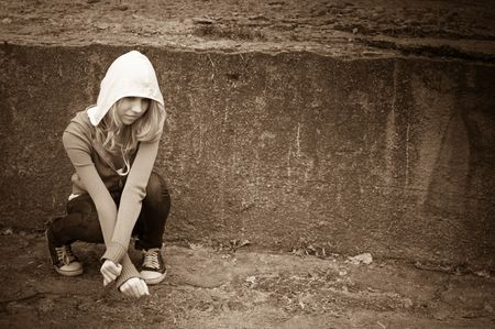 teenage girl siting against wall in a depressed state Stock Photo - 6106666