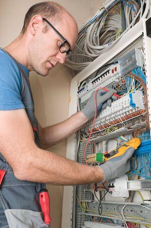 contador electrico: electricista realizar conexiones en el panel principal de electical