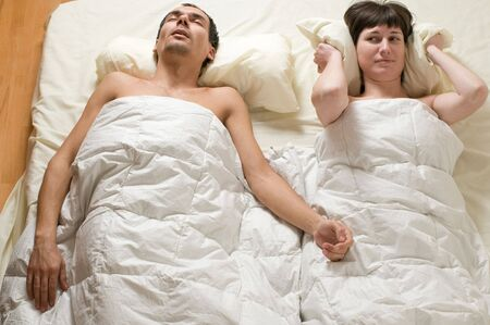 snoring: couple in bed with man snoring