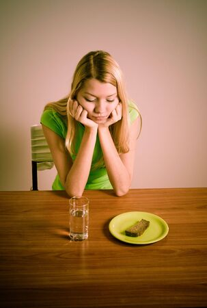 girl sitting at table with bread and glass of water