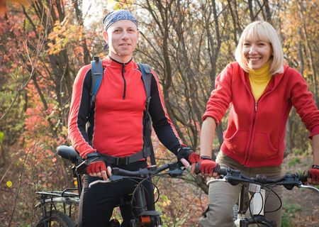 two cyclist biking in autumn forest photo