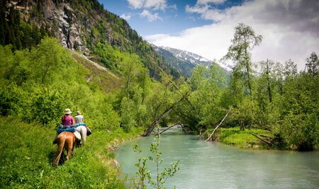 horses in the wild: couple riding on horses in mountains Stock Photo