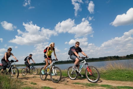 andando en bicicleta: Grupo mixto de ciclistas al lado del r�o