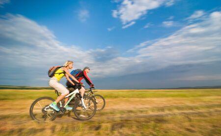 two cyclists biking in motion Standard-Bild