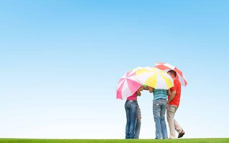 people with umbrellas on green grass Standard-Bild