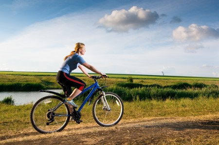 girl relax biking in summer meadow Stock Photo