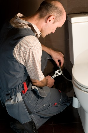 plumber using a pipe wrench to repair a sink