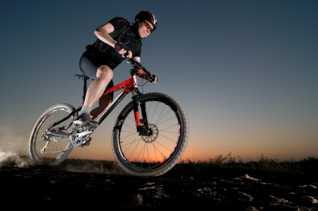 cycling   helmet: man extreme biking at sunset Stock Photo