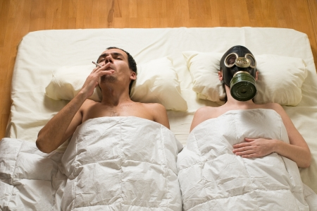 man lying in bed and smoking Stock Photo