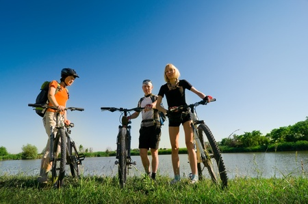 mixed group of cyclists beside river Stock Photo - 8656808