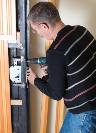 door lock: handyman repairing lock with drill
