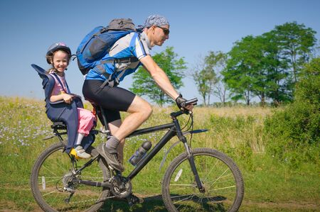father with daughter cycling in summer photo