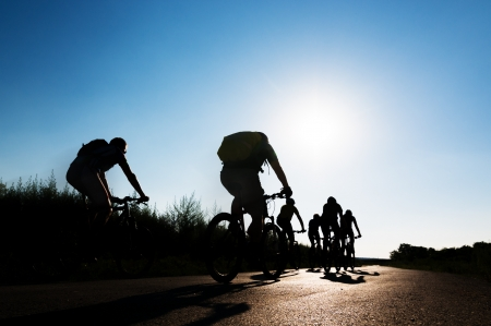 cycling silhouette: group of cyclists biking in motion
