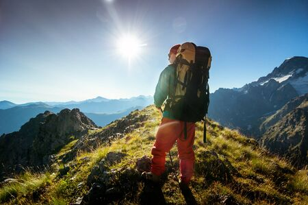 man hiking in mountains with backpack photo