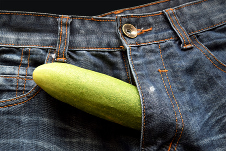 adult education: cucumber is the mark of penis in jean Stock Photo