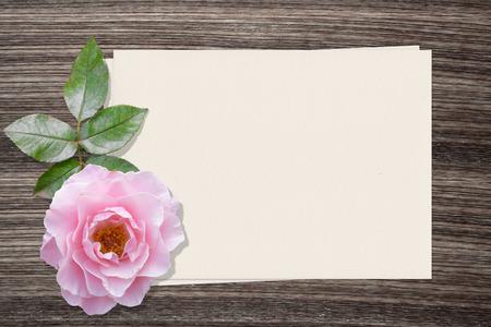 lapiz y papel: Rosa rosa y y papel sobre fondo de madera
