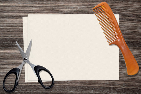 textured paper: comb, scissors and paper on wood background